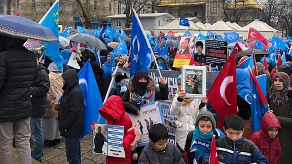 Demonstrators wave Uyghur nationalist flags in central Istanbul as they hold up photos of missing relatives caught up in China