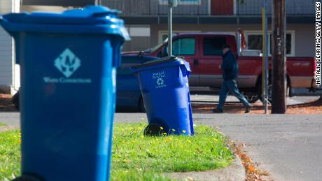 On a residential street in Portland, Oregon, blue wastebaskets can be seen. Coca-Cola will leverage insights from its Atlanta program to scale its recycling efforts.