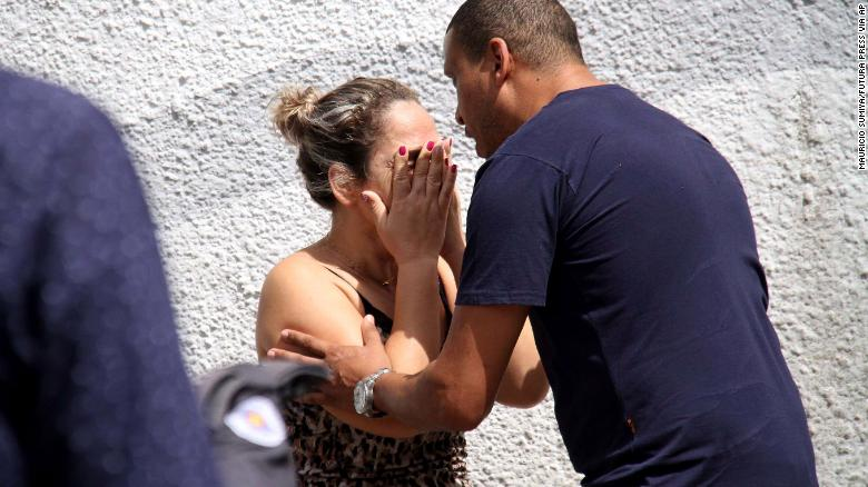 A man comforts a woman at the Raul Brasil State School in Suzano, Brazil, Wednesday, after officials said two teenagers began shooting.