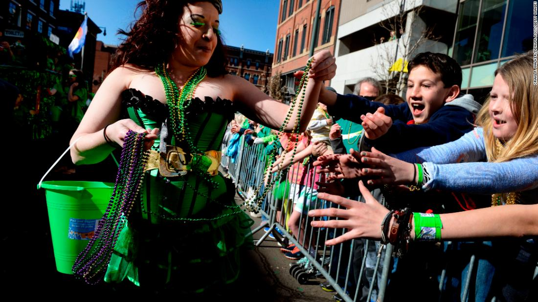 <strong>Denver:</strong> Sarah Gohn of Pub on Pearl hands out beads to youths during the 2015 parade.