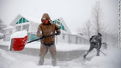 Martin Thompson clears snow from a sidewalk Wednesday in Casper, Wyoming.
