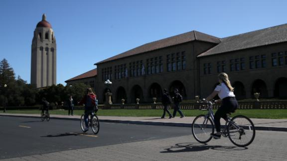 STANFORD, CA - MARCH 12: Cyclists ride by Hoover Tower on the Stanford University campus on March 12, 2019 in Stanford, California. More than 40 people, including actresses Lori Loughlin and Felicity Huffman, have been charged in a widespread elite college admission bribery scheme. Parents, ACT and SAT administrators and coaches at universities including Stanford, Georgetown, Yale, and the University of Southern California have been charged. (Photo by Justin Sullivan/Getty Images)