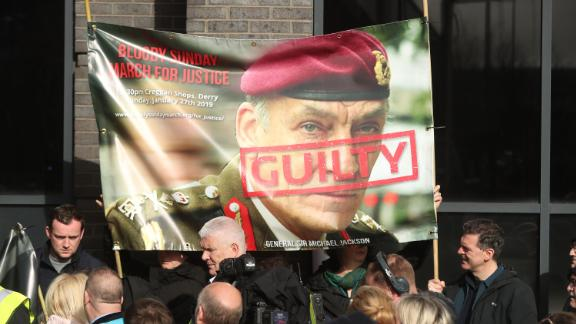 Protesters hold a poster showing British General Sir Michael David Jackson ahead of the announcement on Thursday.