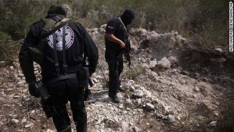 Police officers stand next to a mass grave near San Fernando, Mexico, in 2011. At the time, authorities said a  drug gang was kidnapping passengers from buses and hiding their victims in hidden graves.