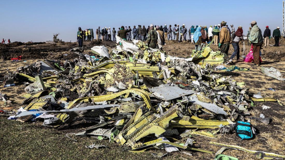 "People stand near collected debris at <a href=""https://www.cnn.com/2019/03/11/world/gallery/ethiopia-plane-crash-intl/index.html"" target=""_blank"">the crash site of Ethiopia Airlines Flight ET302</a> on Monday, March 11. The plane went down near Bishoftu, Ethiopia, after reporting technical problems."