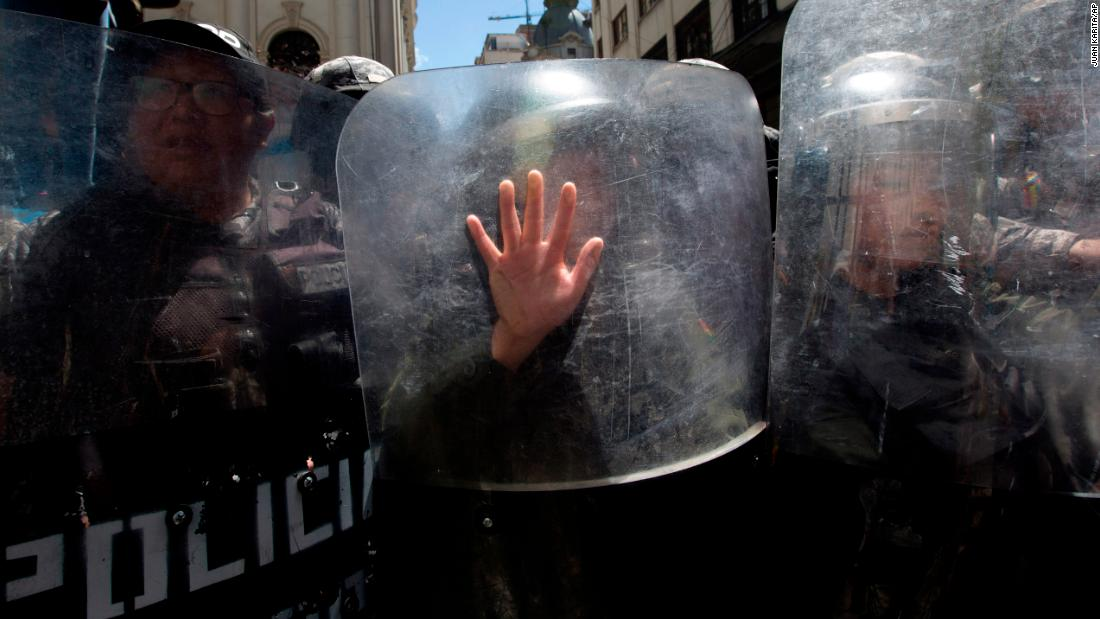 A police officer places her hand on a shield as she helps to keep an International Women's Day march from reaching the government palace in La Paz, Bolivia, on Friday, March 8.