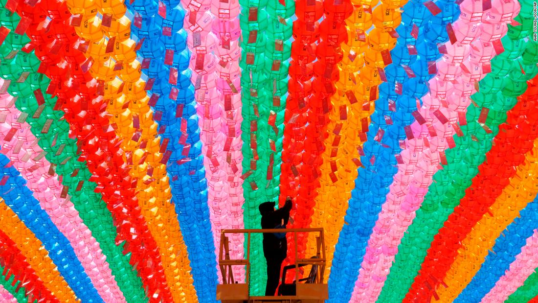 A worker attaches tags bearing the names of Buddhists to lanterns hanging in the Jogyesa Temple in Seoul, South Korea, on Wednesday, March 13. Similar lanterns will be displayed in all Buddhist temples around South Korea for the upcoming celebration of Buddha's birthday on May 12.