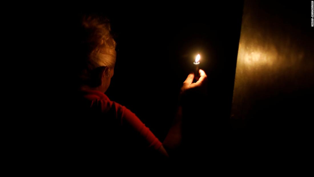 "A woman uses a candle during a blackout in Caracas, Venezuela, on Saturday, March 9. Venezuela's largest source of power <a href=""https://www.cnn.com/2019/03/12/americas/venezuela-struggle-power-intl/index.html"" target=""_blank"">had a catastrophic failure</a> on March 7. At its worst, 19 of 23 states were affected, and Caracas was blanketed by darkness."
