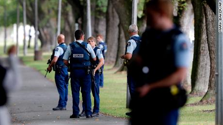 Police keep watch at a park near one of the mosques attacked on Friday.