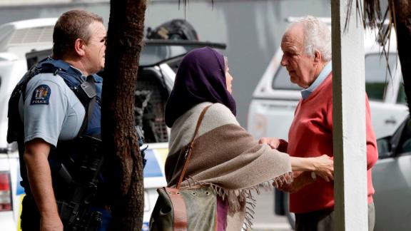 Police escort people away from outside a mosque in central Christchurch after the shootings.