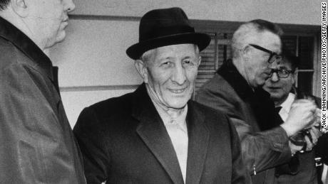Boss mob Carlo Gambino smiles while standing in handcuffs after being arrested by the FBI.