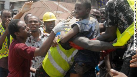 Emergency personnel rescue a child at the site of a building which collapsed in Lagos on March 13, 2019.