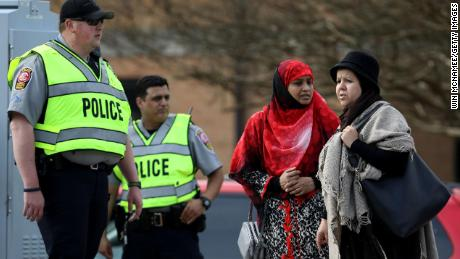 American Muslims stand outside with police officers on March 15 at the Dar Al Hijrah Islamic Center in Falls Church, Virginia.