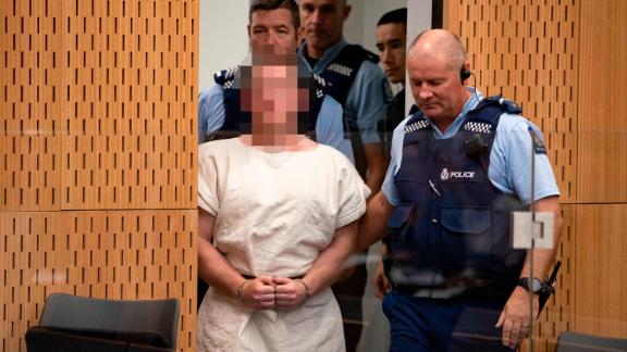 Tarrant is escorted into Christchurch District Court on Saturday. The judge ruled pictures of the suspect in court must have his face blurred.