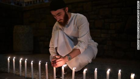 A good believer helps to light dozens of candles while serving the victims before d pay tribute to a hospital in Christchurch on Saturday.