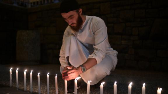 A well-wisher helps to light 49 candles as he pays respects to victims outside the hospital in Christchurch on March 16, 2019, after a shooting incident at two mosques in the city the previous day.