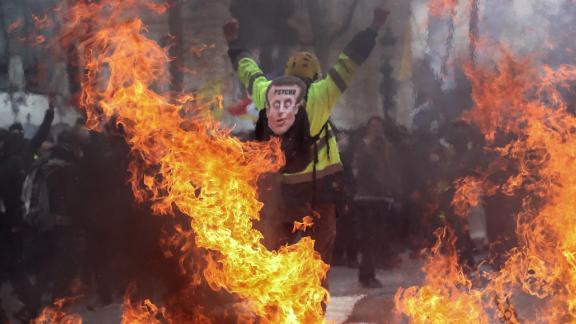 A Yellow Vest protester wearing a mask depicting French President Emmanuel Macron gestures behind flames rising from barricades, in Paris on March 16, 2019.