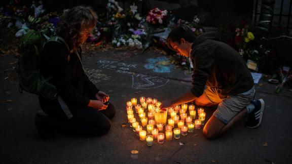 CHRISTCHURCH, NEW ZEALAND - MARCH 17: People light candles next to flowers and tributes laid by the wall of the Botanic Gardens on March 17, 2019 in Christchurch, New Zealand. 50 people are confirmed dead, with 36 injured still in hospital following shooting attacks on two mosques in Christchurch on Friday, 15 March. 41 of the victims were killed at Al Noor mosque on Deans Avenue and seven died at Linwood mosque. Another victim died later in Christchurch hospital. A 28-year-old Australian-born man, Brenton Tarrant, appeared in Christchurch District Court on Saturday charged with murder. The attack is the worst mass shooting in New Zealand