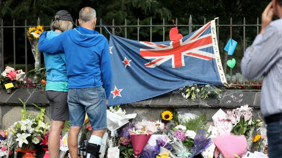 People pay their respects at a memorial outside the Botanical Gardens as a tribute to victims of the mosque attacks in Christchurch on March 17, 2019. At least 50 people were killed and 36 injured in mass shootings at two mosques in the New Zealand city of Christchurch Friday, 15 March. A 28-year-old Australian born, man Brenton Tarrant, appeared in Christchurch District Court on Saturday charged with murder.  (Photo by Sanka Vidanagama/NurPhoto via Getty Images)