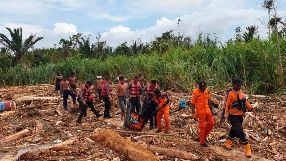 A photo from Indonesia's National Search and Rescue Agency (BASARNAS) shows the agency's personnel and police carrying the body of flood victim in Indonesia's Papua province on Sunday.