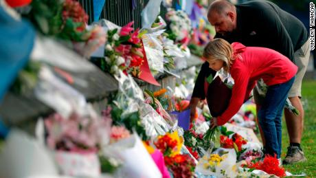 The mourners place flowers on a wall on Saturday in the Botanical Garden in Christchurch.