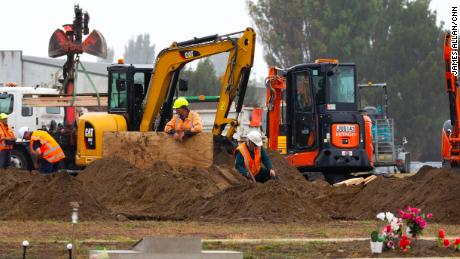 Diggers are working behind a white screen fence to dig graves for some of the 50 people who died on Friday's terrorist attack.