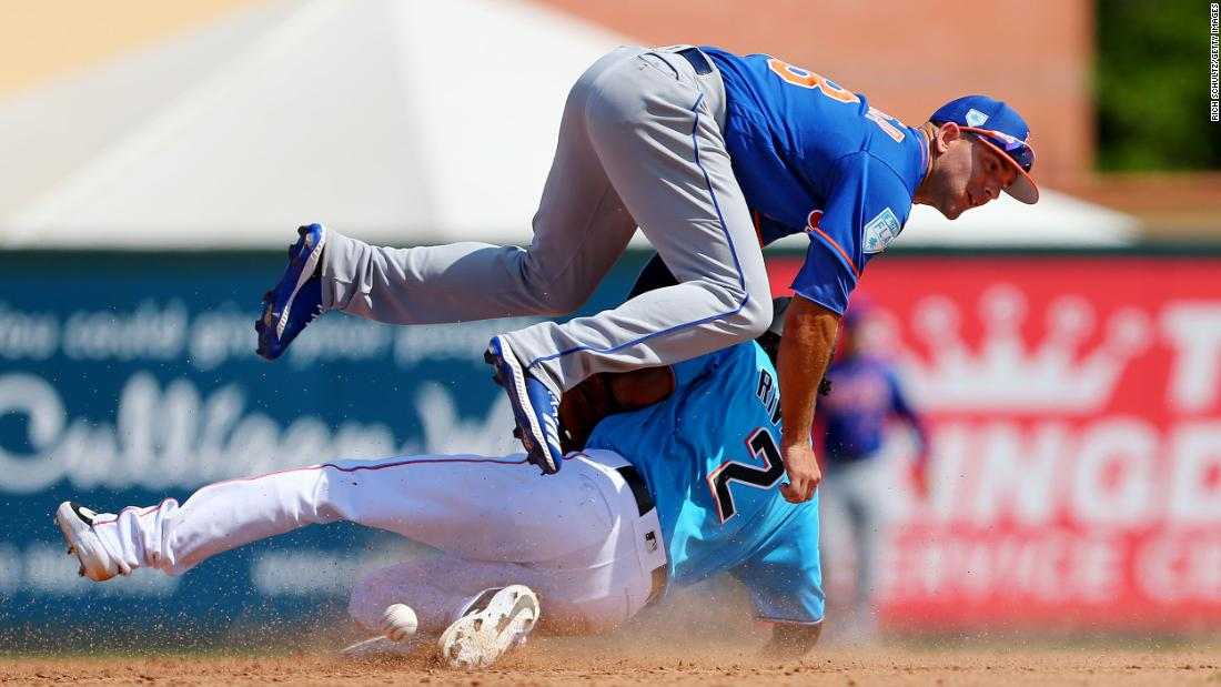 Yadiel Rivera, bottom, of the Miami Marlins steals second base as he upends second baseman Danny Espinosa of the New York Mets during the seventh inning of a spring training baseball game at Roger Dean Stadium in Jupiter, Florida, on Tuesday, March 12.