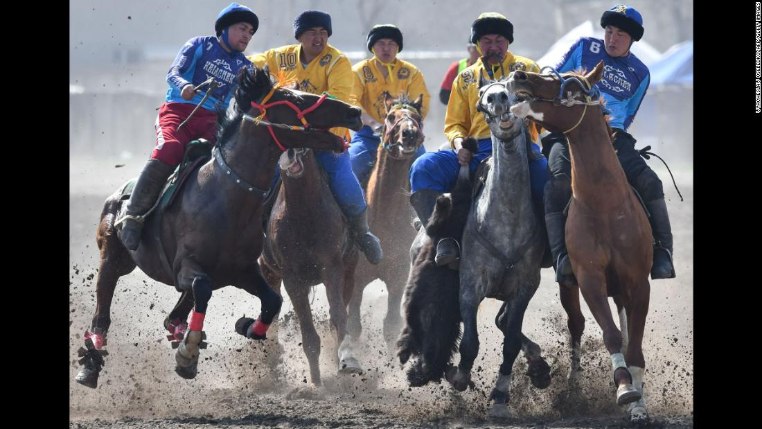 Kyrgyz riders play the traditional Central Asian sport of Kok-Boru (Gray Wolf) or Buzkashi (Goat Grabbing) in Bishkek, Kyrgyzstan, on Saturday, March 16. Mounted players compete for points by throwing a stuffed sheepskin into a well.