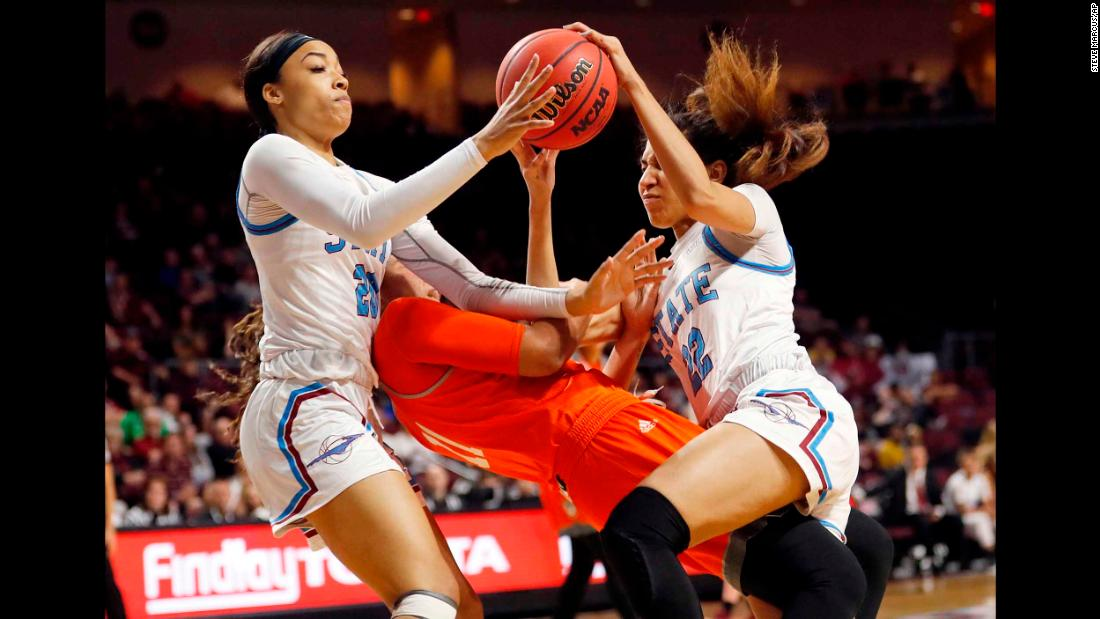 New Mexico State guard Dominique Mills, left, and teammate Kalei Atkinson, right, go after a loose ball over Texas-Rio Grande Valley guard Quynne Huggins during an NCAA college basketball game in the championship of the Western Athletic Conference women's tournament in Las Vegas on Saturday, March 16.