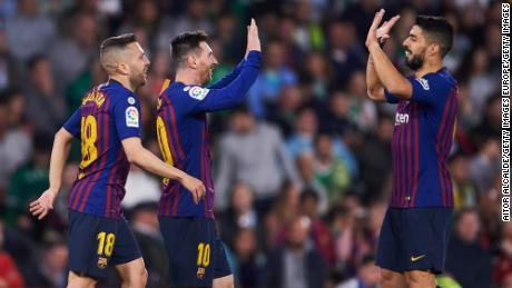 Messi celebrates with Suarez and Jordi Alba after scoring Barca's second goal of the night