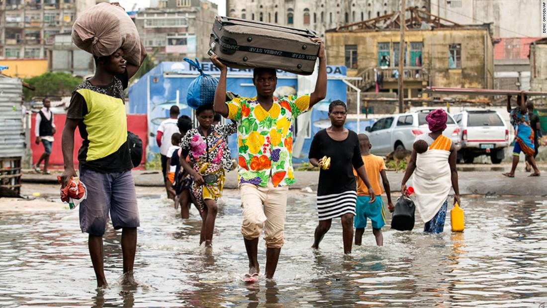 People carry their personal effects in the aftermath of Cyclone Idai in Beira on Friday, March 15.