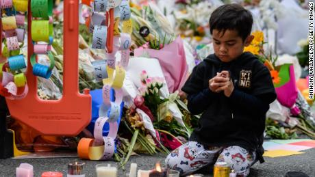 A child sits among flowers and candles left in tribute to the victims after a vigil in Christchurch on March 18, 2019, three days after a shooting incident at two mosques.