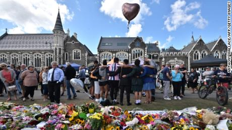 A group of students sings in front of a flower tribute to the victims of the mosques in Christchurch.