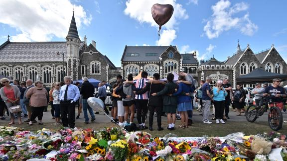 TOPSHOT - A group of students (C) sings in front of flowers left in tribute to victims at the Botanical Garden in Christchurch on March 19, 2019, four days after a shooting incident at two mosques that claimed the lives of 50 people. - New Zealanders have begun handing in weapons in response to government appeals following the Christchurch massacre, but the gesture has put some squarely in the social media firing line. (Photo by Anthony WALLACE / AFP)        (Photo credit should read ANTHONY WALLACE/AFP/Getty Images)