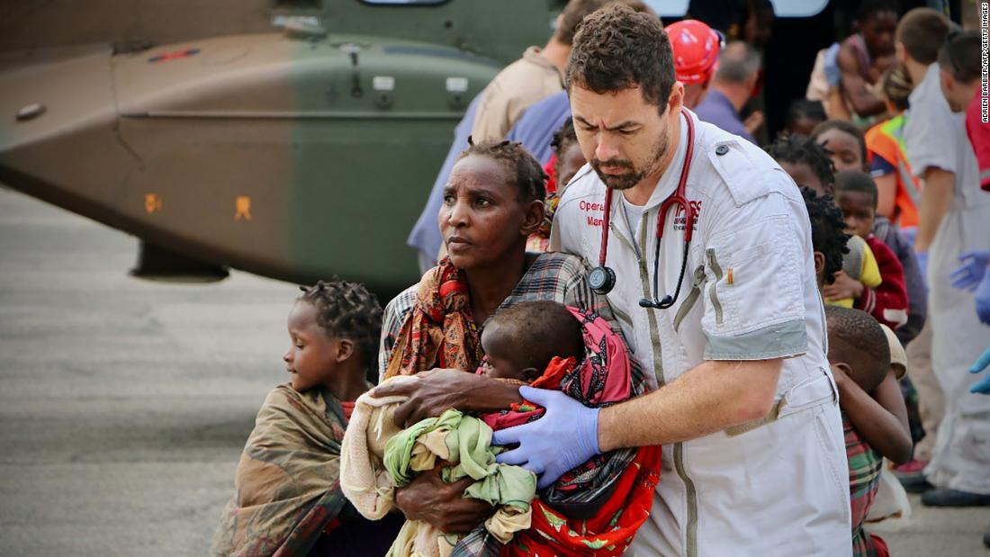 Survivors are escorted to safety by aid workers at the airport in Beira on March 19.