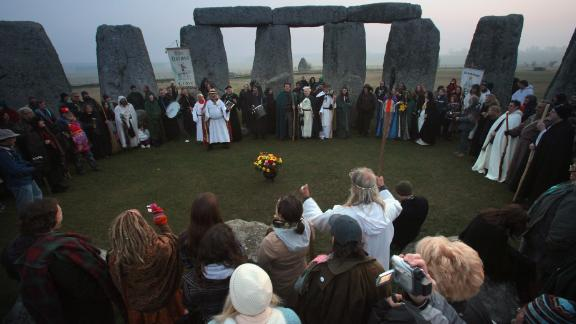 Druids wait for the sun to rise as they celebrate the spring equinox at Stonehenge.