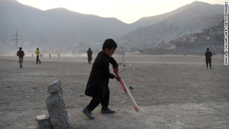 An Afghan boy bats in front of a makeshift set of stumps at an esplanade at Shuhada Lake in Kabul -- a city now obsessed by the sport.