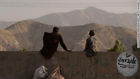 "A pair of young Afghans sit on a wall as they watch a game on the outskirts of Kabul. ""When I started filming them, they didn't have a grass pitch in the whole country. A lot of the guys had never played with a leather ball,"" Albone reflects."