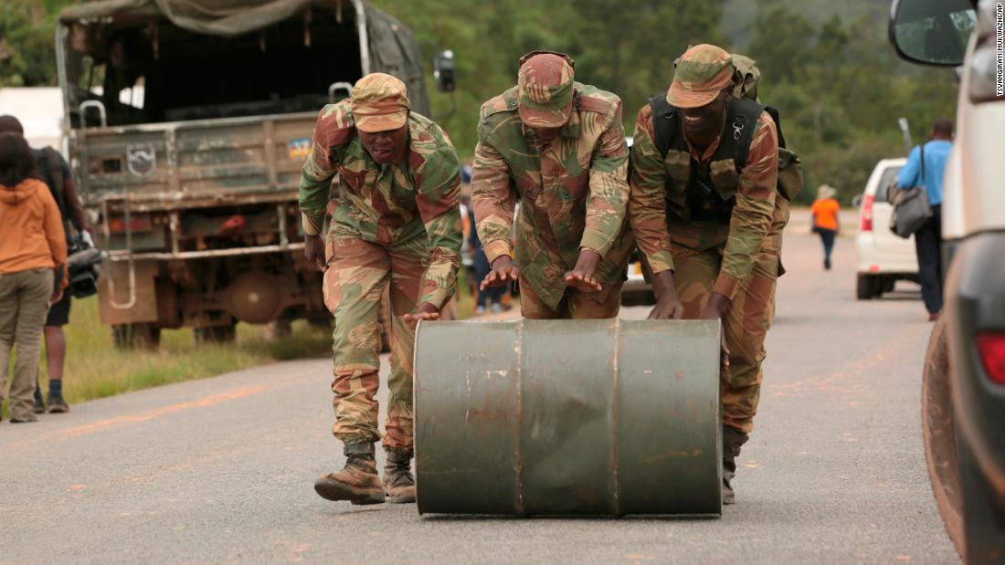 Soldiers push a drum of jet fuel used for rescue operations in Chimanimani on March 19.