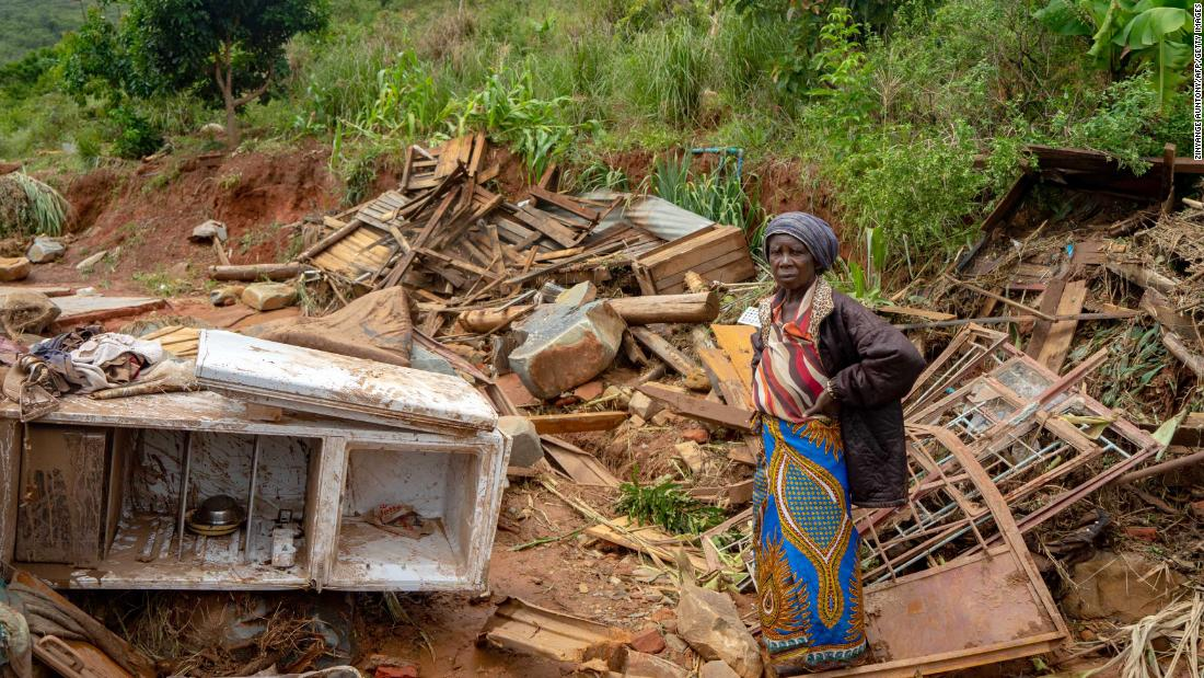 An elderly woman stands amid her destroyed belongings on March 19 in Chimanimani, an area on the border of Mozambique and Zimbabwe.