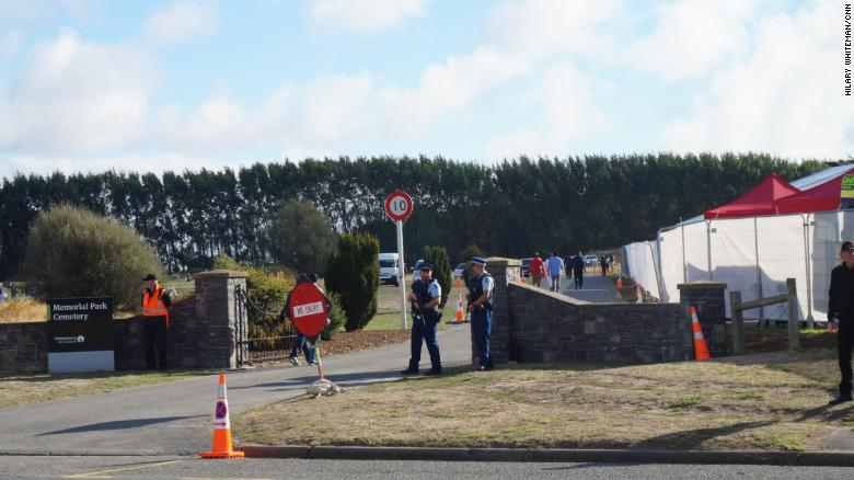 New Zealand police guard the entrance to Memorial Park Cemetery, where the first of 50 people killed in Friday's shooting will be buried.