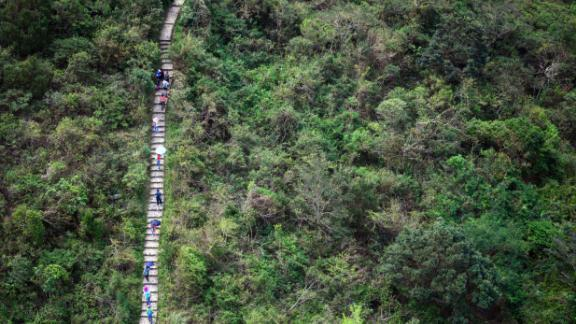 In this photo taken on October 7, 2018, hikers walk along the Ngong Ping Trail on Lantau island in Hong Kong.