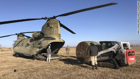 Nebraska Army National Guard soldiers load bales of hay into a CH-47 Chinook helicopter for airdrops to cattle stranded by flooding Wednesday in Columbus, Nebraska.