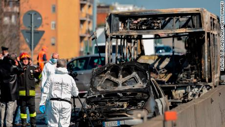 Italian police officers and firefighters work by the wreckage of a school bus after it was hijacked and set alight by its driver.
