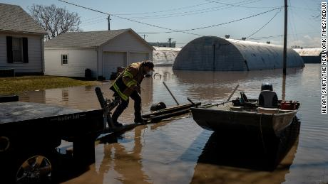 Bryce Moran loads a boat back onto a truck after going to look at his office and seeing that it was completely flooded, in Hamburg, Iowa, March 20, 2019. Hamburg residents held back the Missouri River in 2011, then had to tear down the improvised levee that saved them. Much of the town is now under water. (Hilary Swift/The New York Times)