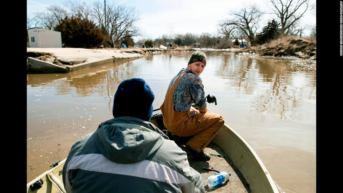 Helmut Shea Kaukver III and Tim Rockford navigate their neighborhood in a boat after major flooding in Bellwood, Nebraska, on Monday, March 18. The Midwest flooding killed livestock, ruined harvests and has farmers worried for their future.