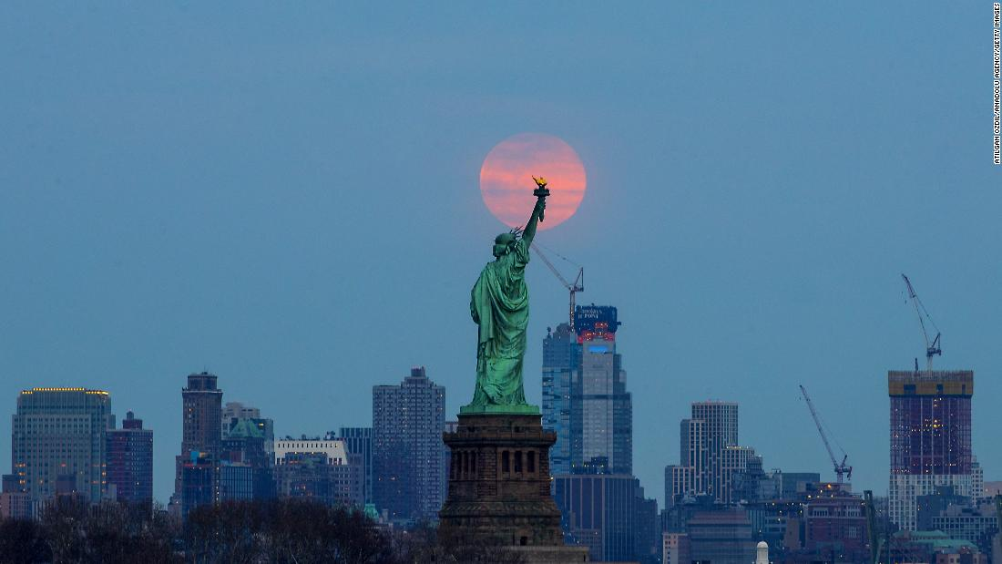 The last supermoon of 2019 -- the Super Worm Equinox Moon -- rises behind the Statue of Liberty in New York City on Wednesday, March 20.