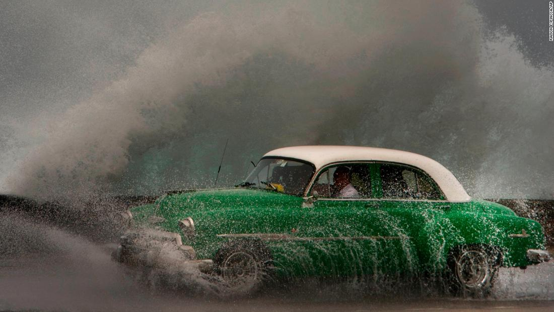 Waves crash against the Malecon sea wall as a taxi drives past in Havana, Cuba, on Tuesday, March 19.