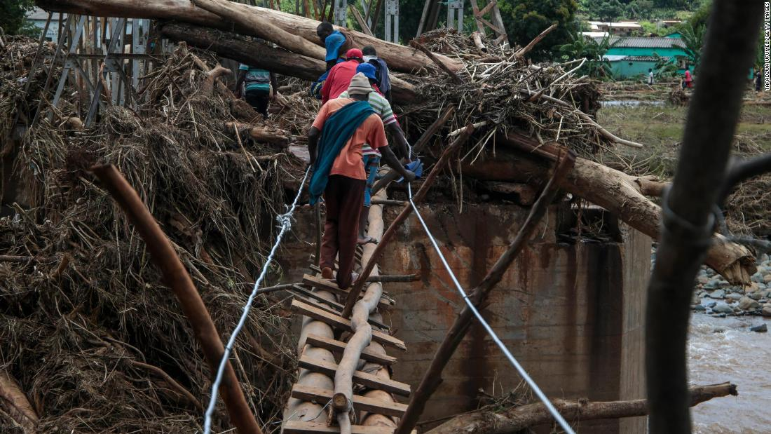 People cross a makeshift bridge over a river on Wednesday, March 20, that surged days earlier during Cyclone Idai in Chipinge, Zimbabwe.