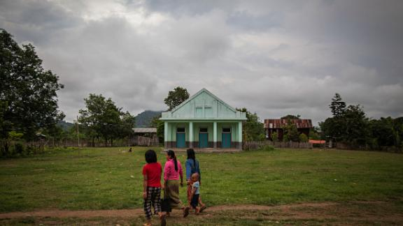 Residents of the Jan Mai Kawng Internal Displacement Camp, which is sponsored by the Kachin Baptist Church walk past a church on the camps property on June 7, 2014 in Myitkyina, Myanmar.